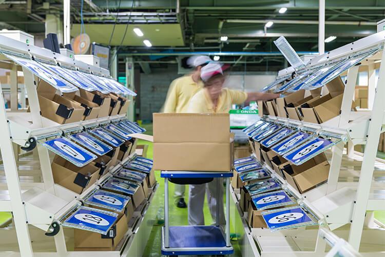 シャッター式仕分けシステムを使用した商品の仕分け作業の様子